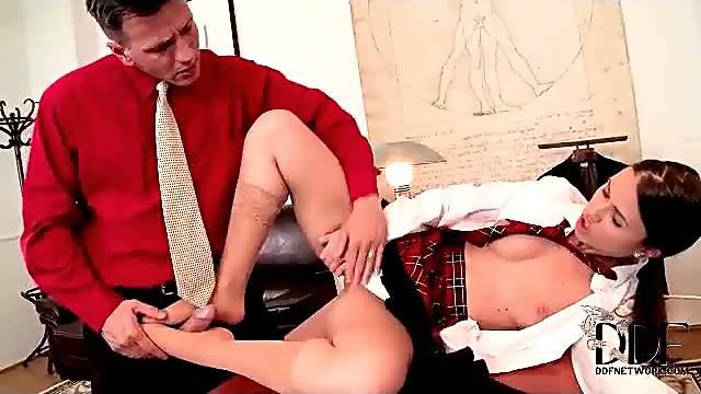 Schoolgirl in tan stockings gives great footjob