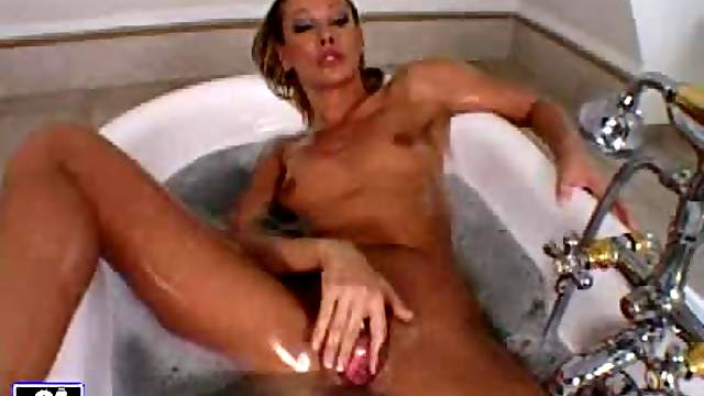Sandy plays with her shaved pussy while taking a bath