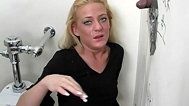 A horny blonde strokes and sucks some black cock in a gloryhole