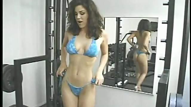 Brilliant solo model in bikini masturbating passionately using toy in the gym