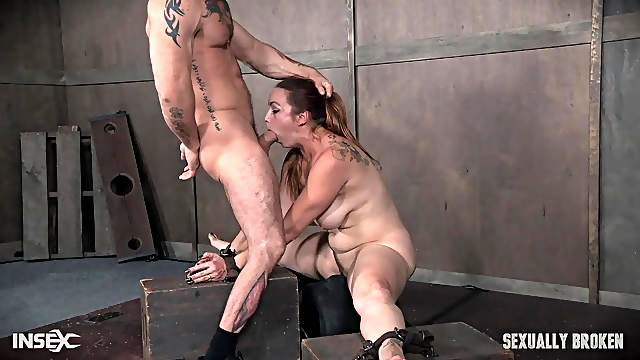 Bella Rossi has her hands tied to a table and throat abused hardcore