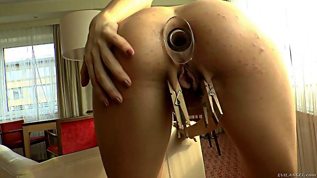 Toying with a dildo and attaching clothespins to her labia
