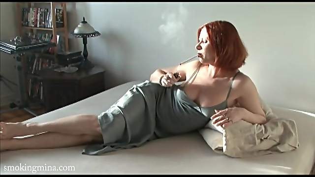 Redhead in a lovely satin dress smokes cigarette