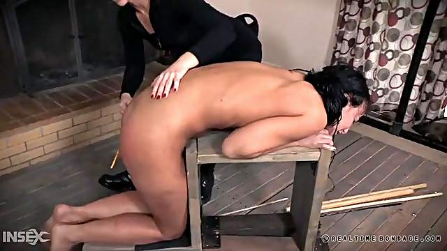 Caning her ass as the girl cries in pain