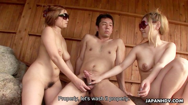 Two tender Japanese babes suck on a big cock